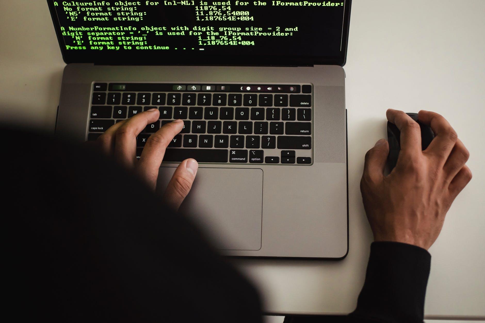 crop faceless programmer working on laptop in studio
