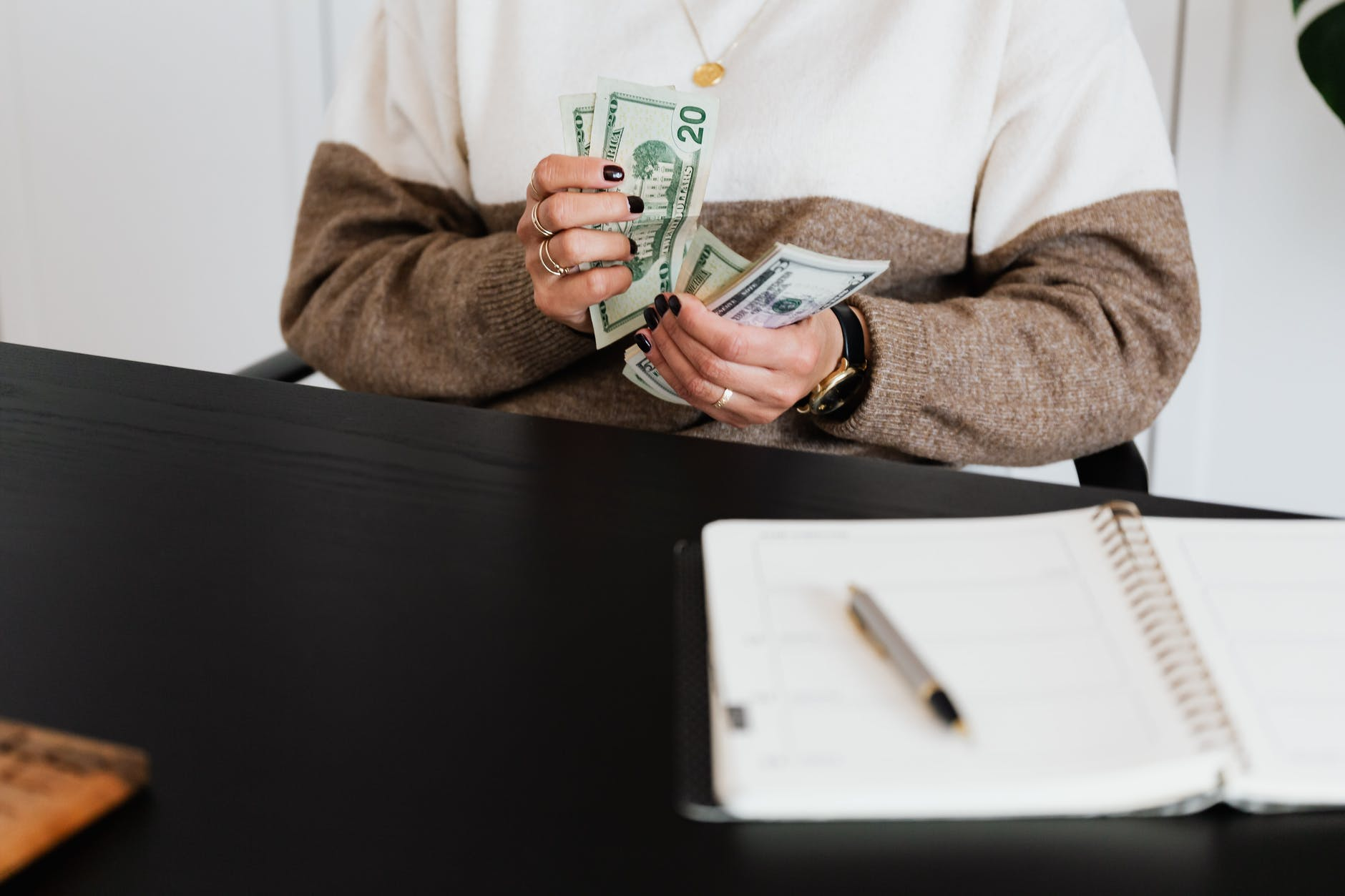 a person in sweater counting her money