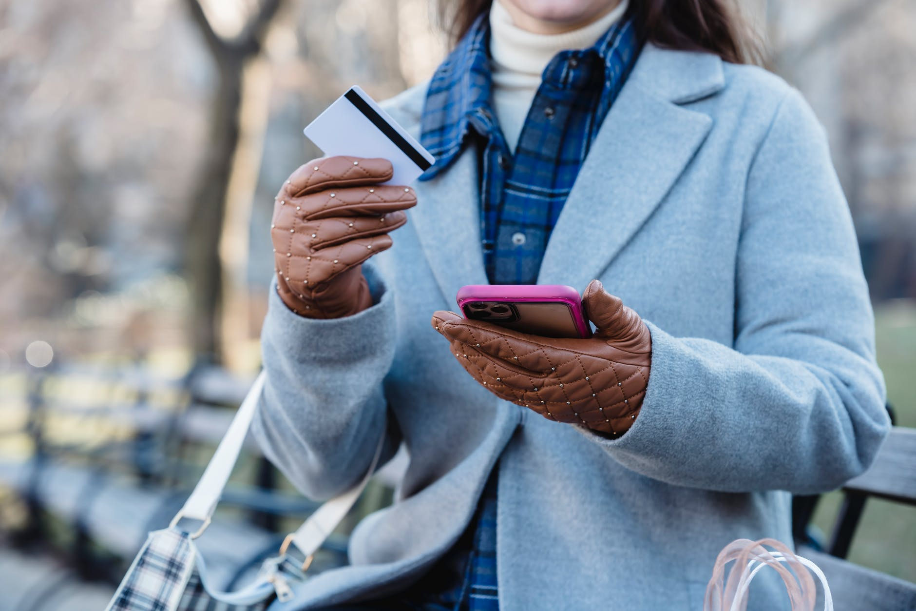 woman using smartphone and holding credit card while sitting in park